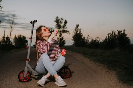 woman blowing soap bubbles and sitting on the scooter. summer fun activities  . 스톡 콘텐츠