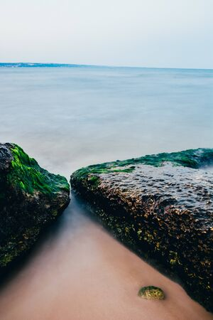 close up beach with big rocks covered with moss . long exposure with selective focus.