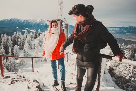 a guy with a girl in winter climb the highest mountain in Romania . couple love concept .