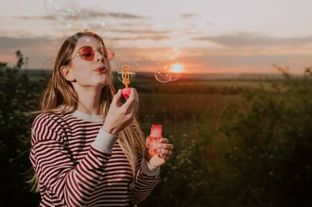 woman blowing soap bubbles . summer fun activities