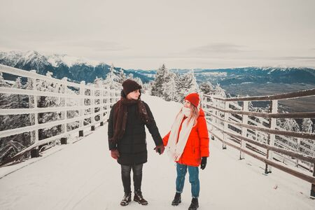 couple holding hands and looking at each other on a high mountain in Romania .