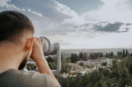 man watch in telescope with city skyline Imagens