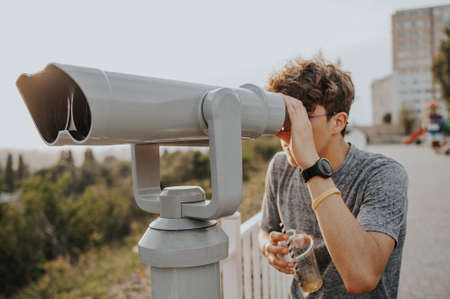 man with cocktail watch in telescope with city skyline