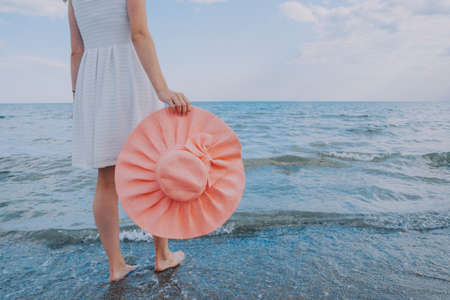girl with pink hat walks along the beach