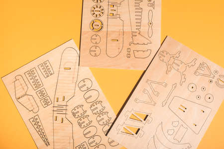 scattered spare parts from a wooden airplane constructor on a yellow background . 스톡 콘텐츠