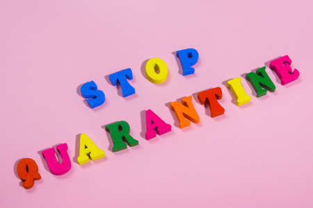 word STOP QUARANTINE made of wood letters.  multi colored tablets around the word   . 스톡 콘텐츠