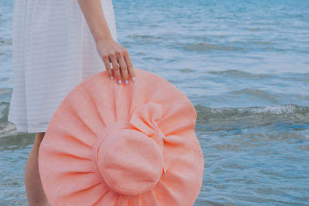woman in a white dress holds pink hat along the blue sea 스톡 콘텐츠