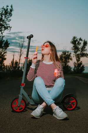 woman blowing soap bubbles and sitting on the scooter.