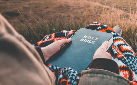 girl is looking at the holy bible at sunrise  on hill .