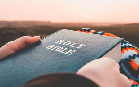 girl reads the bible at sunrise  on hill .