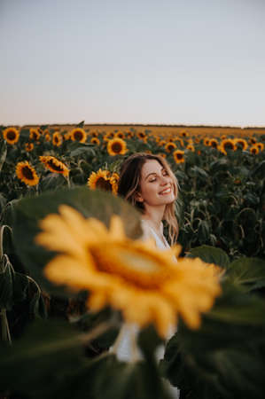 portrait of a smiling girl in a sunflower field 스톡 콘텐츠