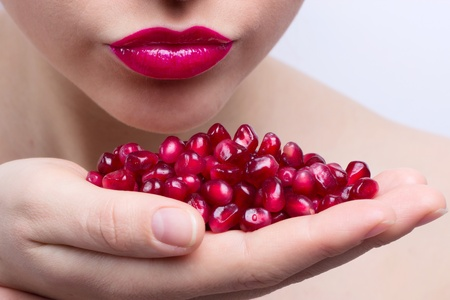 a pomegranate: young beautiful woman with seeds of pomegranate