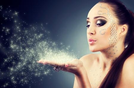 beautiful girl blowing magic stars