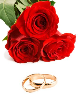 wedding bands: Two gold wedding bands beside a red roses.