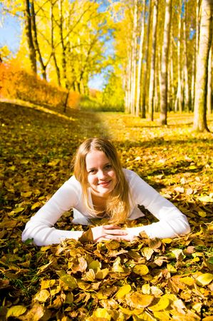 Young pretty woman on the autumn leaf photo