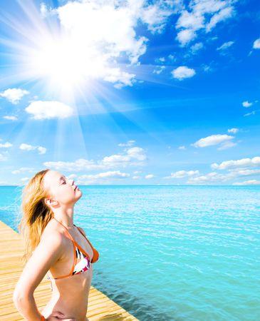Beautiful young woman relaxing near the sea photo