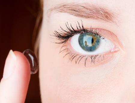 globo ocular: Cerca de insertar un lente de contacto en el ojo femenino