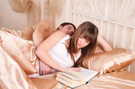 woman reading a book and  man sleeping next to her.  Stock Photo - 9303556