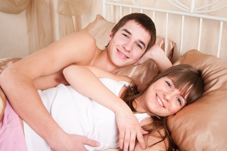 Young happy couple in bed Stock Photo - 9303559