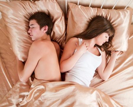 angry couple: Par molesto por separado dormir en su cama  Foto de archivo