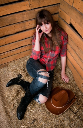 barn boots: Beautiful smiling cowgirl in hay