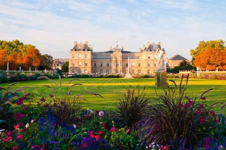 Jardin du Luxembourg with the Palace and statue. Few flowers are in front and blue sky behind.  Фото со стока