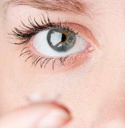 lentes de contacto: Cerca de insertar un lente de contacto en el ojo femenino