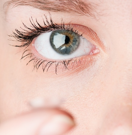 Close up of inserting a contact lens in female eye