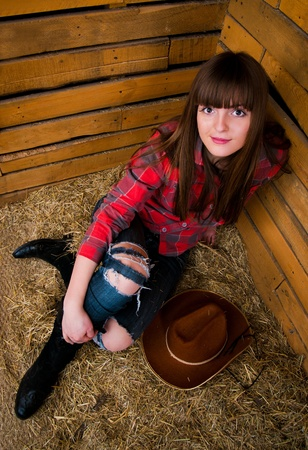 Beautiful smiling cowgirl in hay photo