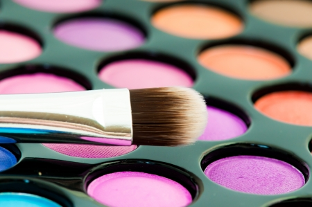 cosmetics collection: multicolored eye shadows with cosmetics brush  Stock Photo