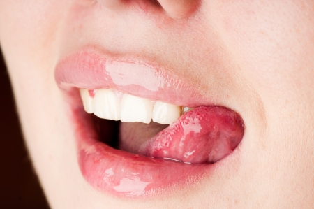 Detail of young female licking her pink lips  Stock Photo
