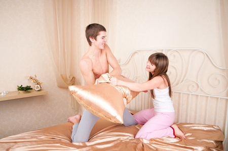 Young couple fighting pillows in the bedroom  photo