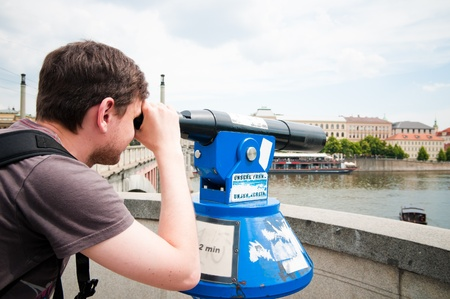 The man looks through telescope in Prague photo
