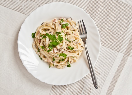 Spaghetti . Fettuccine carbonara in a white bowl, garnished with bacon, mushrooms and parsley. Delicious creamy sauce. photo