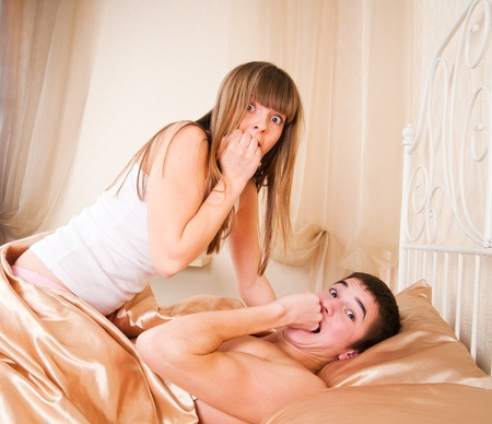 Surprised sex couple lying in bed  photo