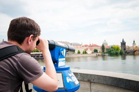 The man looks through telescope in Prague photo