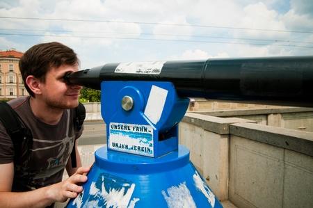 The man looks through telescope in Prague