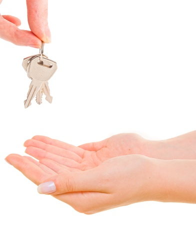 Female hand holding keys and handing it over to another person.  photo