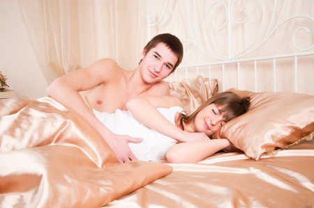 Happy young couple lying in bed and man looks at woman Stock Photo - 14298960