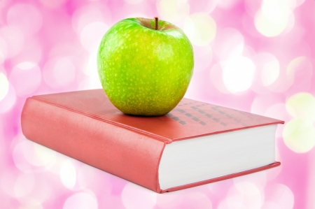 A green apple on a book   with pink lights in the background  photo