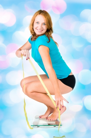 Happy woman on weight scale  with blue lights in the background  photo