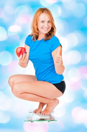 Woman with red apple crouching on scale  photo