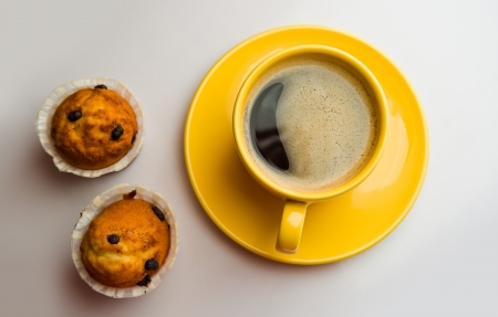 Coffee in an yellow cup and muffins photo