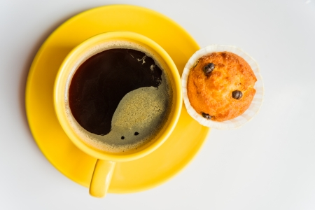 Coffee in an yellow cup and a muffin  photo