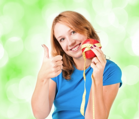 Portrait of a young sport woman holding apple and measuring tape  photo