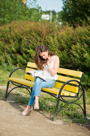 adult magazines: Woman read a magazin in park Stock Photo