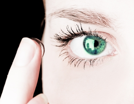 lentes de contacto: Primer plano de la inserción de una lente de contacto en el ojo de mujer