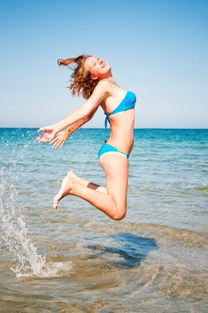 young girl jumping out of a water  photo