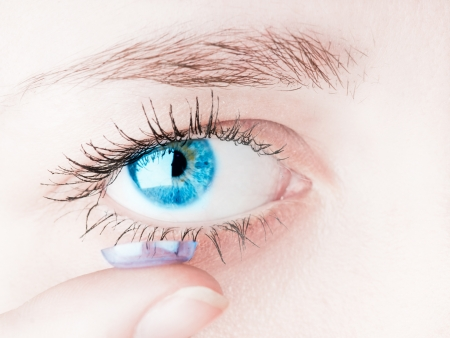 lentes de contacto: Primer plano de la inserci�n de una lente de contacto en el ojo de mujer