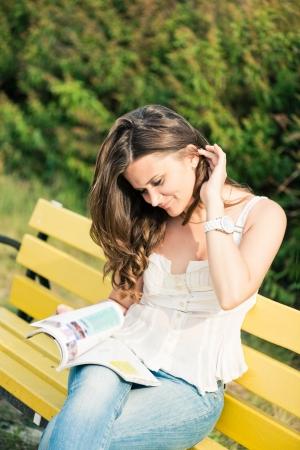 Frau eine Zeitschrift lesen im Park